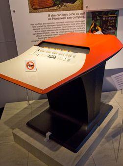Honeywells kjøkkendatamaskin kostet bare rett over 10 000 dollar. I bakgrunnen en reklameplakat fra sekstitallet;
