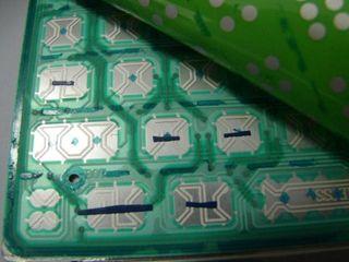 Slik ser lagene med membran ut, i et vanlig, tynt tastatur. Brukeren har lagt over små teipbiter for å dekke over hullene ned til det nederste membranet, for å stoppe tastene fra å registreres.