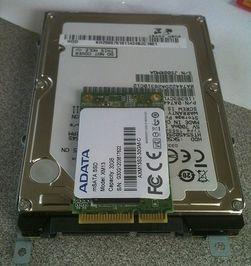 En mSATA SSD på toppen av en 2,5-tommers SATA harddisk.