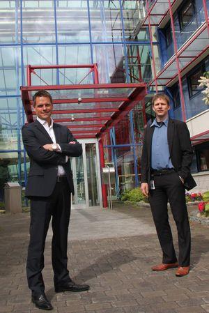 """Vidar Vorpenes (venstre) og Steinar H. Nygaard foran inngangen til det spektakulære Canon-bygget på Holmlia."