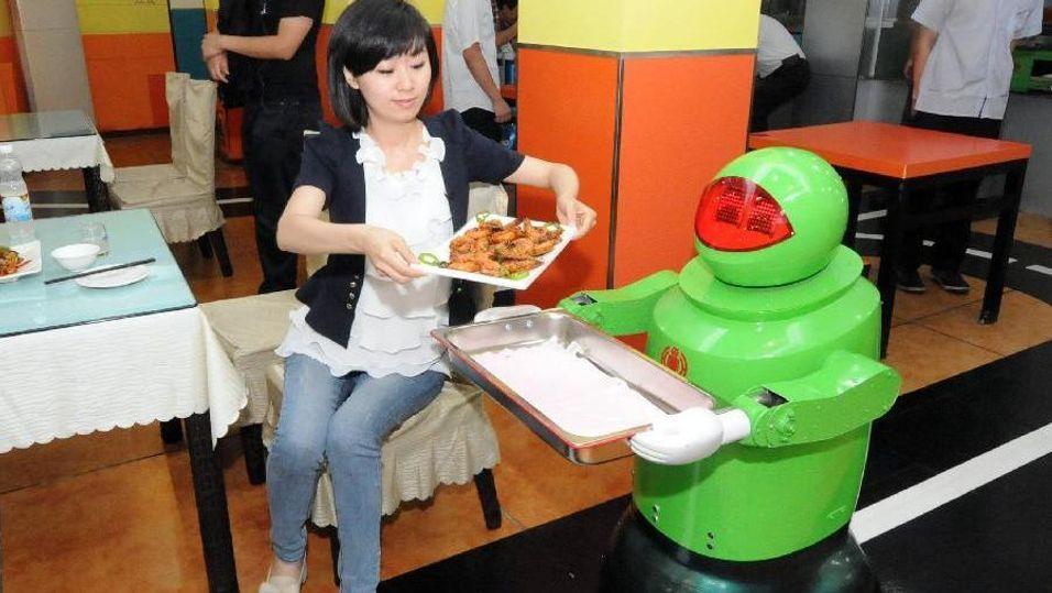 Her får en kvinne maten servert av en robotservitør.