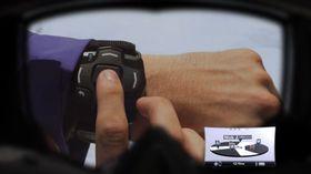 Fjernkontrollen festes på håndleddet og kan styre brillenes funksjoner.