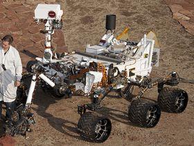 Hvis du trodde Curiosity var en søt liten Wall-E-robot, må du tro om igjen. Her står en forsker ved siden av roveren på et testområde i California.