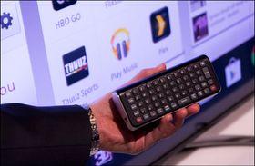 Fjernkontrollen til Google-TV-ene kommer med fullt tastatur. Legg også merke til Plex-logoen i bakgrunnen.