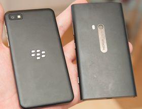 Slik ser baksiden på BlackBerry Z10 ut ved siden av en Nokia Lumia 920. Bakdekselet er avtagbart og skjuler batteri, plass for SIM-kort og minnekort.