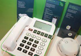 Doro Secure 350 er en fasttelefon med mottaker for de ulike sensorene. Ved siden av, en røykvarsler som kan kobles til.
