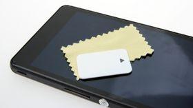 Er dette verdens minste pusseklut? Den følger med, sammen med en liten dings for å fjerne plastfilmen foran skjermen.