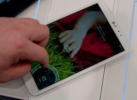 Når du sveiper over låseskjermen åpner det seg en ring rundt fingeren din. Her bruker vi en av snarveiene nederst på skjermen. Sveiper du lenger oppe på skjermen vises skjermbildet bak låseskjermen inni ringen.