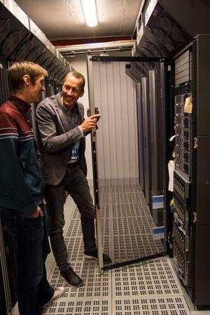 Sverre Reiten, utviklingssjef i Teknologidivisjonen til NRK, holder døren til serverskapet åpen. Ole Andreas Johnsen, prosjektleder i Teknologidivsjonen, følger med.