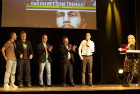 Tor-Steinar Nastad Tangedal (holder mikrofonen), redaktør i Gamer.no, mottar prisen sammen med skribenter og annonseselgere. (Foto: Viktor Jæger)