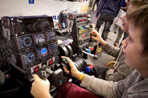 Ivrige deltakere tester en flysimulator fra Mad Catz.