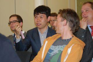 Mediehuset Teks utvikler Alf Marius Foss Olsen (i midten i oransje hettegenser), flankert av Kinas sterkeste sjakkspiller – Wang Hao – og president i Norges sjakkforbund, Jøran Aulin-Jansson (lengst til høyre).