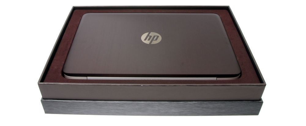 Pen og gullende ren, med HP-logoen i skinnende metall på den trøffelbrune aluminiumbaksiden.