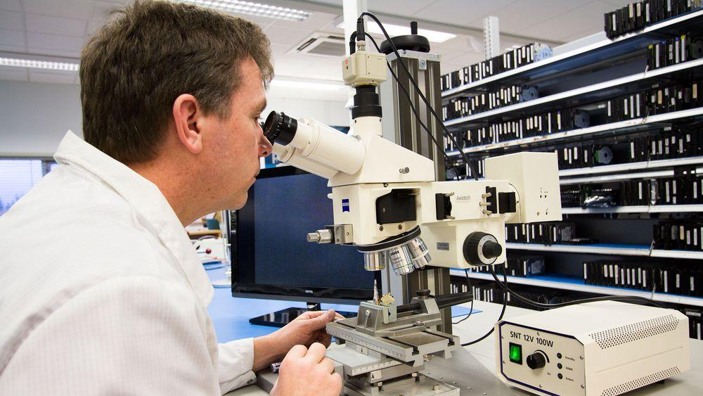 Hans Rønningen, sjef for renrommet til IBAS, studerer lese- og skrivehodet til en harddisk under mikroskop.