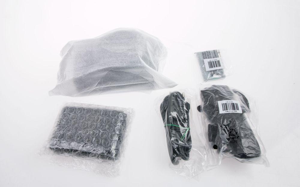 Inni filtposen finner vi kameraet, som er pakket inn i en ekstra pose.  I pappesken finner vi alt det andre du ser på bildet: lader, batteri, strømkabel og reim.