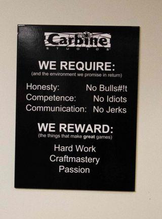En plakat som henger på veggen hos Carbine Studios med hva de krever av sine ansatte. (Bilde: Håvard Hofstad Ruud/Gamer.no).