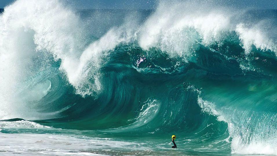Liten fotograf mot store, store bølger.