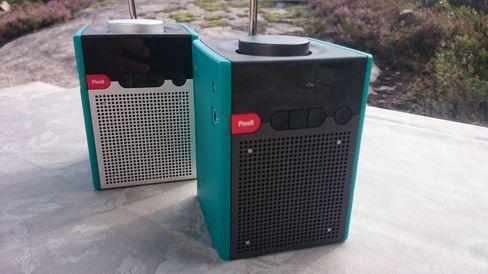 Den fremste radioen er en Pinell Go+, mens radioen i bakgrunnen er den originale Pinell-radioen uten Bluetooth. Den nye versjonen har mørke metallflater.