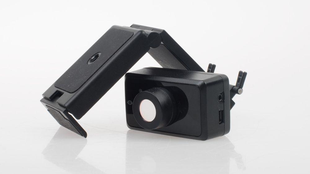 Kameraet er ment å plasseres oppå skjermen, eller på et bord foran brukeren. Det lille stativet kan tilpasses til de fleste bruksområder, og selve kameramodulen kan også tas av dette. Legg også merke til de to inngangene på siden – disse skal vi komme tilbake til om litt.