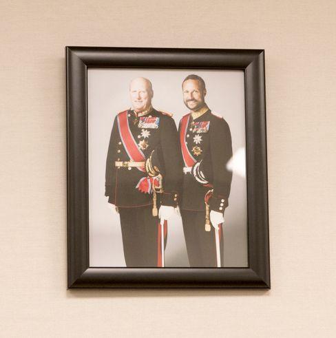 Kongen og kronprinsen pryder veggen på det støysikrede møterommet.