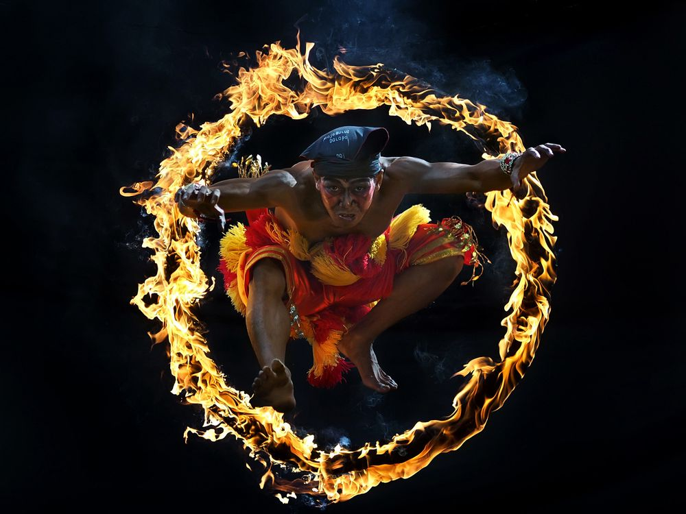 One of traditional attraction in Indonesia Culture called Bujang Ganong. He jumped into the circle of fire.