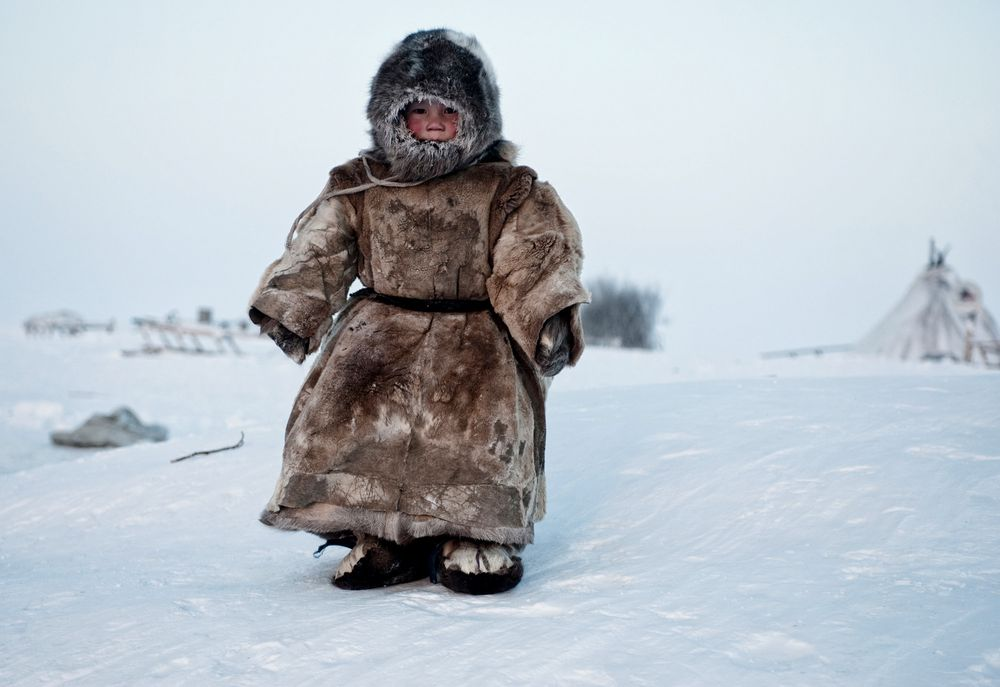 A Young Nenets boy plays in -40 degrees on Yamal in the Winter in Siberia.