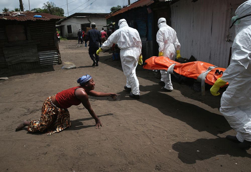 A woman crawls towards the body of her sister as Ebola burial team members take her for cremation on October 10, 2014 in Monrovia, Liberia. The woman had died outside her home earlier in the morning while trying to walk to a treatment center, according to her relatives. The burial of loved ones is important in Liberian culture, making the removal of infected bodies for cremation all the more traumatic for surviving family members.
