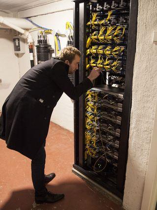 Arve Paalsrud gjør den lille endringen i serverskapet i kjelleren som må til.