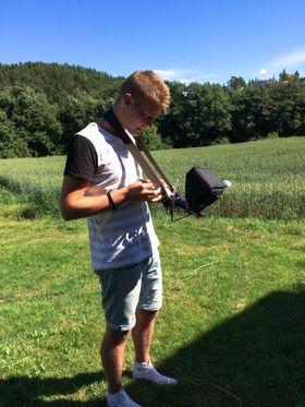 Kim-David Østgård fjernstyrer kameradronen sin, mens han følger med på opptaket.