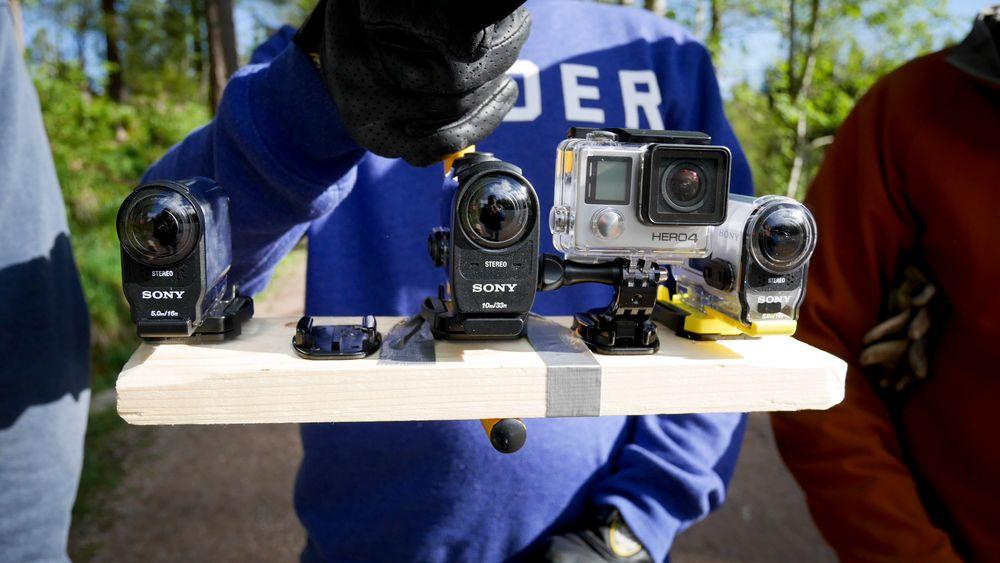 HDR-AS200V til venstre, HFR-X1000V i midten og GoPro Hero 4 Black og den gamle Sony HDR-AS100V til høyre som referansekameraer. Testriggen er laget av en plankebit med håndtaket fra en gammel arbeidslampe, superlim og gaffateip.