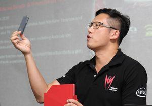 Markedssjef Chris Lee i ASRock viser frem den kombinerte reiseruteren og Miracast-donglen.