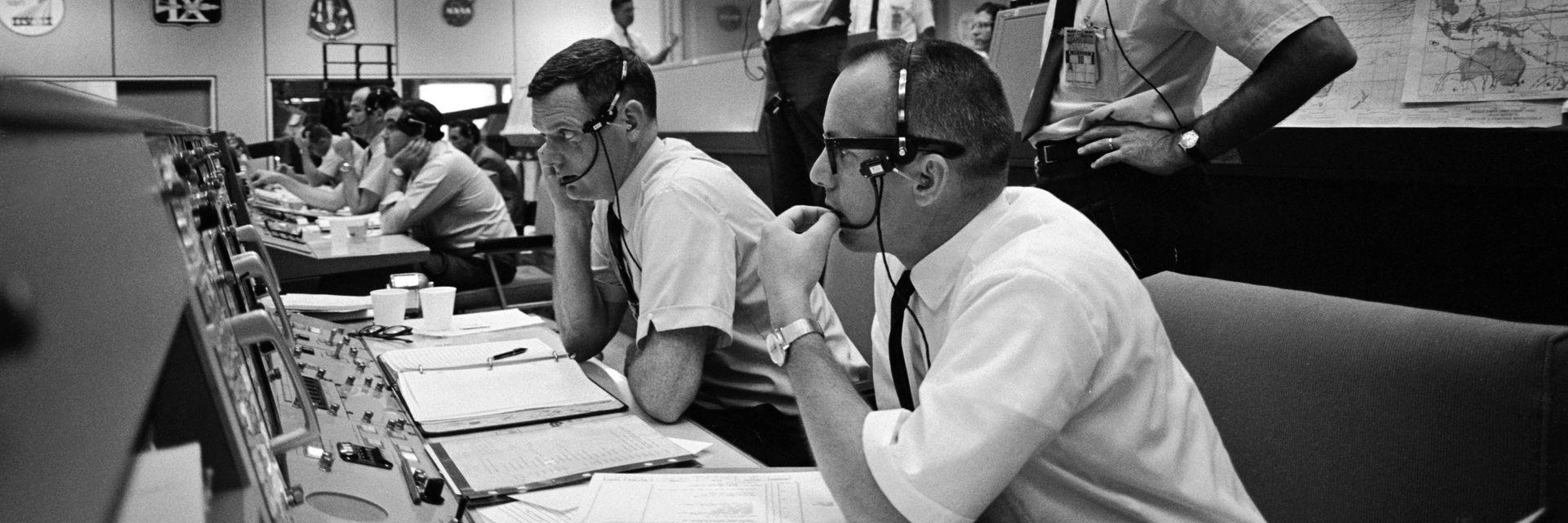 Fra lederkonsollen i kontrollrommet til Apollo-ferdene. På hodet har flygelederne spesielle hodesett som var de første av sin type. De ble konstruert av og var det første produktet til Plantronics.