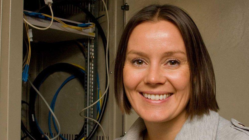 Homenet-sjef Nina Vesterby foran skapet i kjelleren der den lille boksen som leverer bredbånd til leilighetene står.