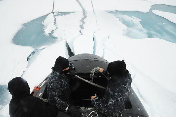 Mannskap på SSN 21 står i tårnet etter å ha brutt opp gjennom isen på Nordpolen.