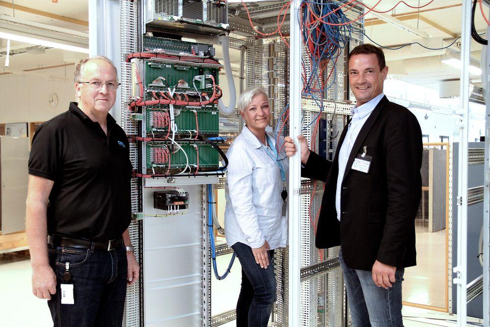 Fra venstre: Harald Albretsen, Monica Metzner fra Origo Solutions og Aron Øksdal fra CCS, her foran et skap under produksjon.
