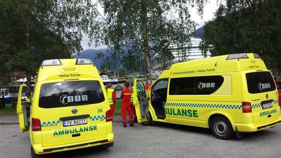 Ambulanse venter på 32 busspassasjerer som skal komme med båt fra Gudvangtunnelen hvor bussen de var i stod i brann.  Foto: Arne Veum / NTB scanpix