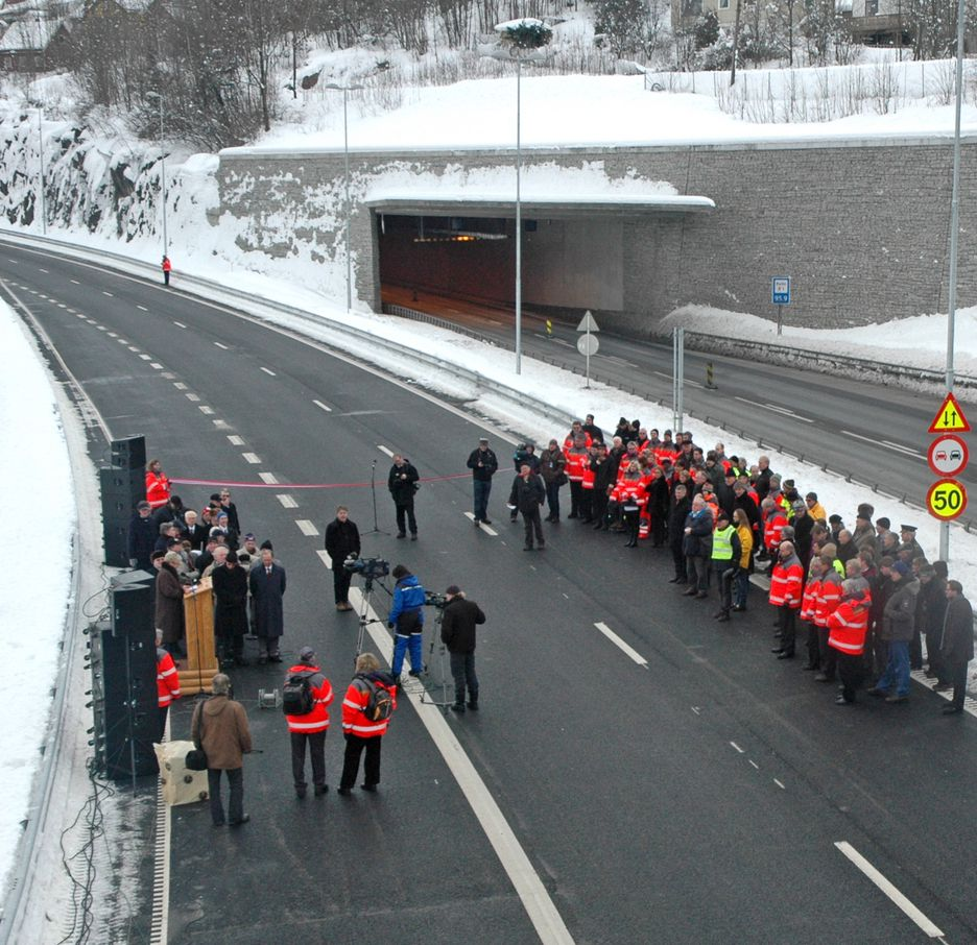 Vegvesenfolk og prominente gjester samlet på Frydenhaug i Drammen for å åpne nordgående kjørebane på E 18. Nordre portal til den 1,8 km lange Kleivenetunnelen ses i bakgrunnen. (Foto: Anders Haakonsen)