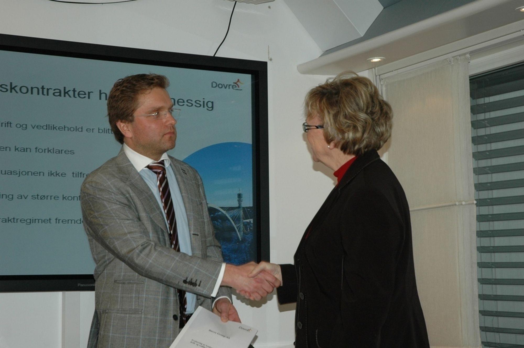 Thorleif Sunde i Dovre Group overleverer evalueringsrapporten om funksjonskontrakter til statsråd Magnhild Meltveit Kleppa.