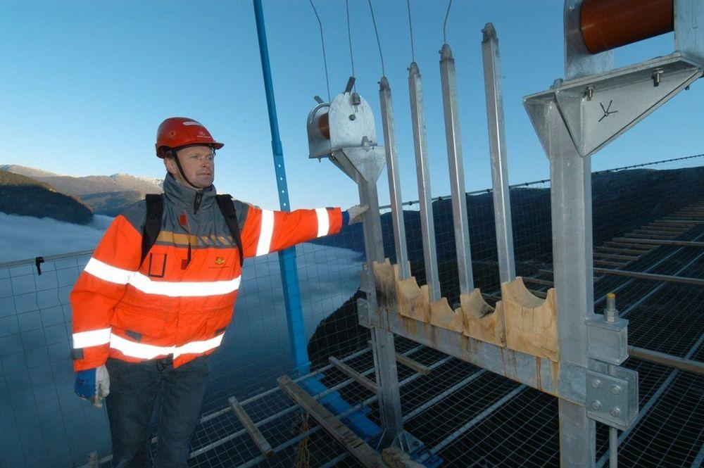 Assisterande byggjeleiar Ingar Fasteland i Statens vegvesen ved ein av kabelformarane ute på gangbrua, der tråden skal leggast inn. (