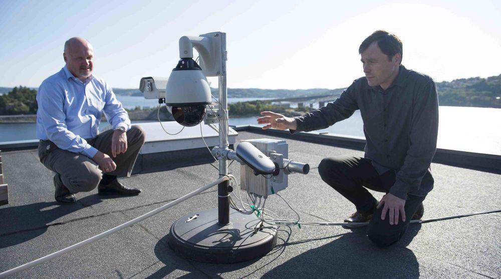 Styreleder Carl-Fredrik Lehland (til venstre) og daglig leder Jan Eide ved en demonstrasjonsnode installert på taket til Polewall ved Vige i Kristiansand. Merk at laserstrålen ikke er synlig, og at den heller ikke kan skade øyet.