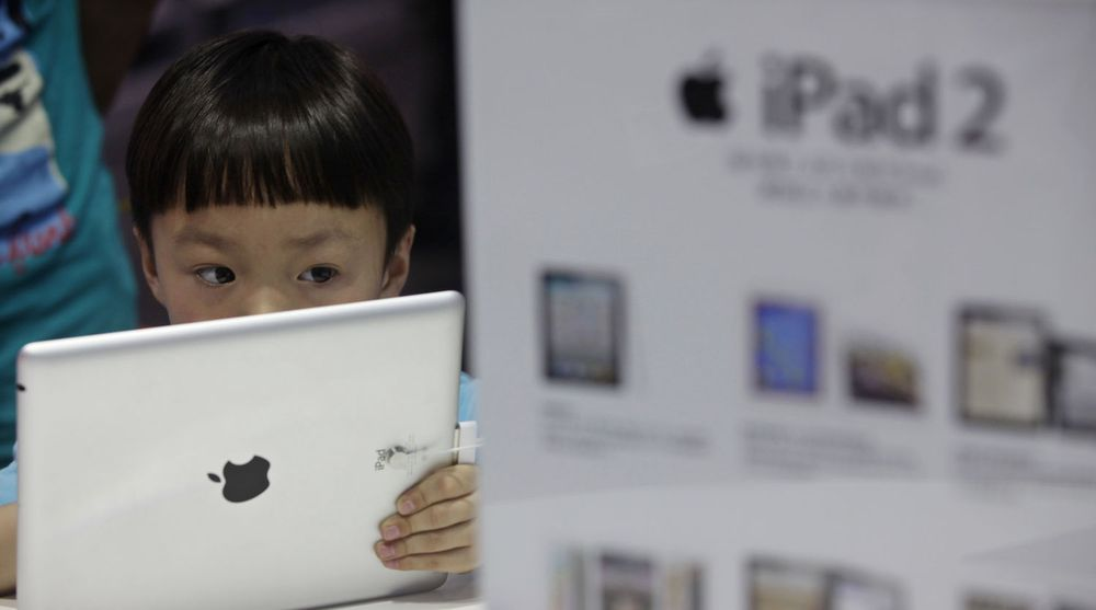 En kinesisk gutt ser på Apples iPad i en butikk i byen Wuhan. Selv om iPad ikke er offisielt til salgs i Kina er etterspørselen og interessen på det grå markedet stor.