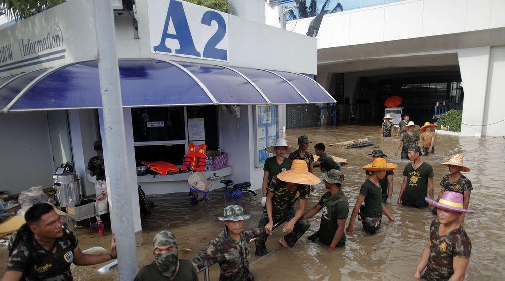 Full stans: Soldater holder vakt ved Western Digitals produksjonsanlegg for harddisker i Thailand, som nå står under vann og er evakuert.