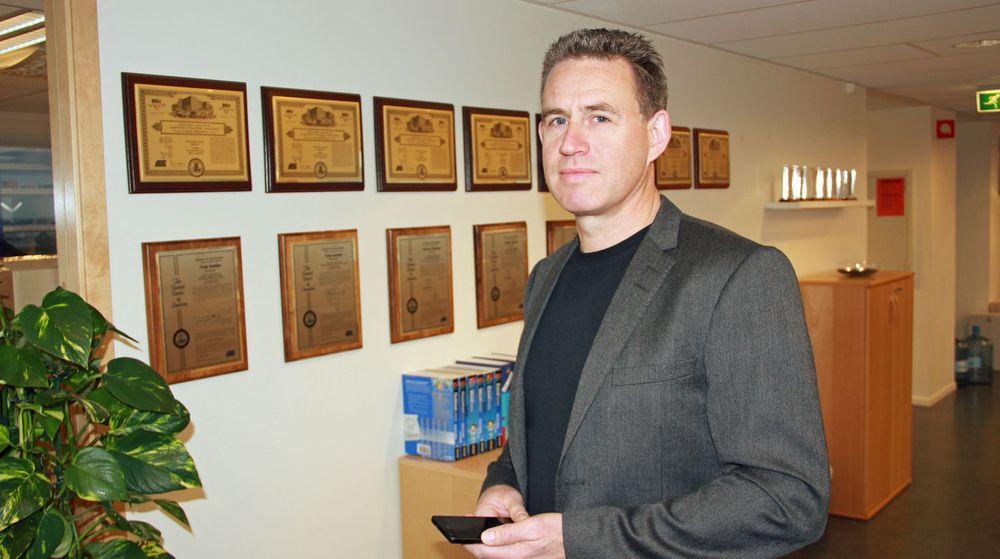 Alf-Egil Bogen, markedssjef for Atmel, viser fram fram noen av patentbevisene til den norske avdelingen. I hånden holder han en Samsung Galaxy S2, en smartmobil som benytter teknologi utviklet ved blant annet Atmel Norway og ARM Norway.