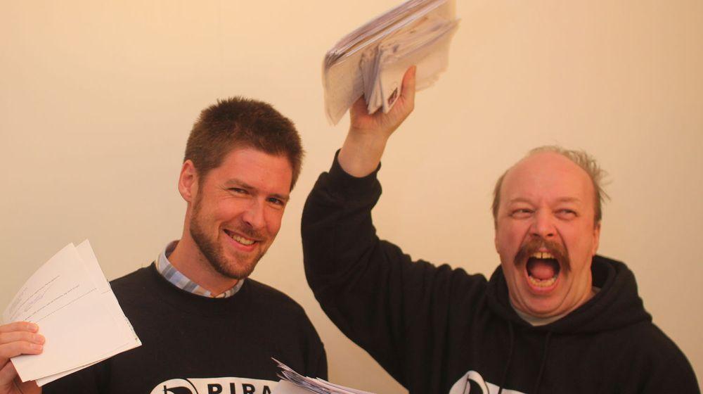 Signatur nummer 5 tusen vises frem av Øystein Sættem Middelthun (t.v), styremedlem i Piratpartiet og leder av partiets IT-gruppe. Leder Geir Aaslid jubler med en bunke ferske signaturer.