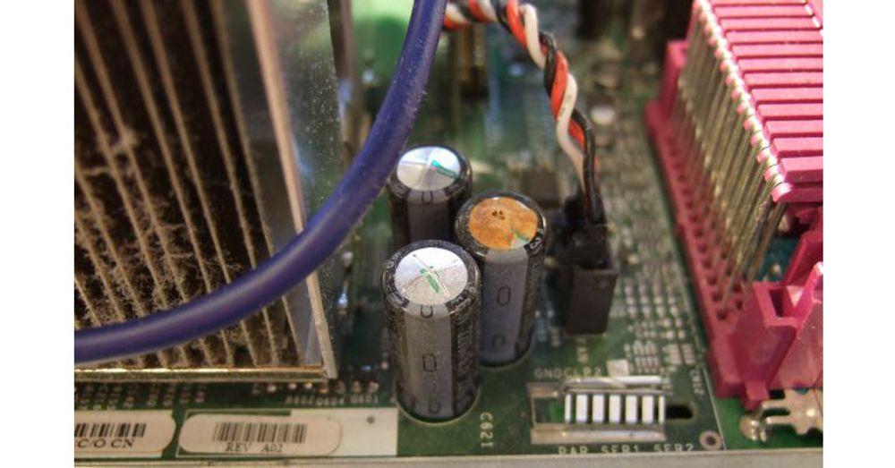 Det brune belegget viser at kondensatoren til høyre har sprunget lekk. Feil på kondensatoren rammer grunnleggende funksjoner på hovedkortet. Lekkasjen kan føre til feil på kretskortet og på andre komponenter.