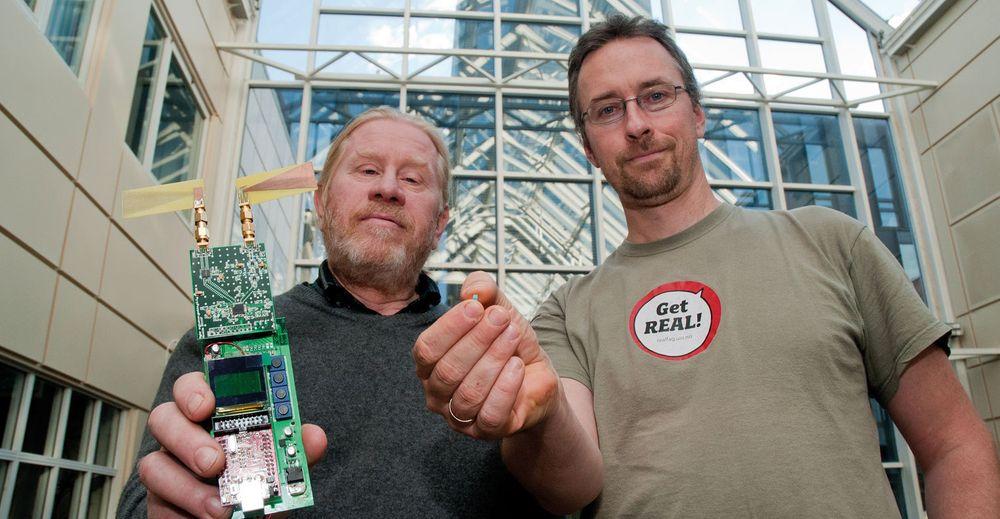 Philipp Häfliger (t.h.) og Tor Sverre Lande ved Institutt for informatikk ved UiO med et apparat som ved hjelp av trådløs energi måler blodsukkeret under huden.