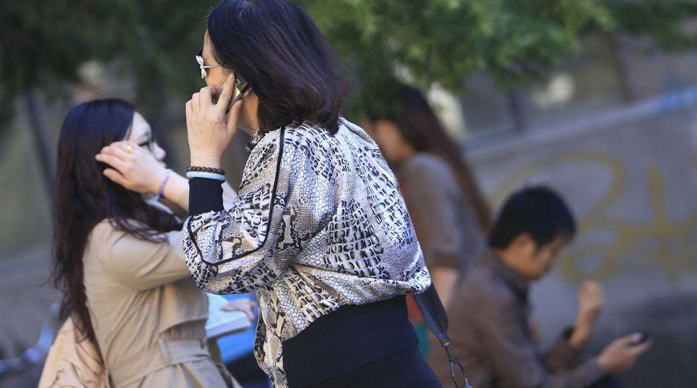 Gatebilde fra Beijing i september i år. Brukere går i stadig større grad over til smartmobiler, helst lokale merker.