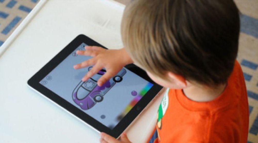 En ung skoleelev er opptatt med fargelegging (eller er det fargelære?) på i iPad. Nå strømmer paddene inn i norsk skole, viser tall fra tilrettelegger.
