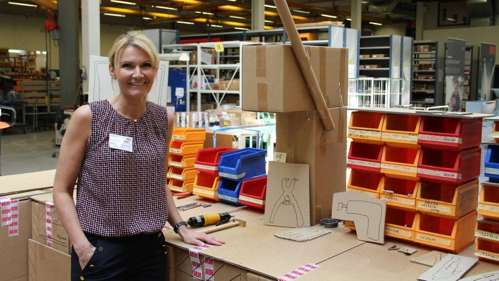 Heidi Svensen foran en arbeidsstasjon i kartong – som har dannet grunnlaget for bestilling av ny skreddersydd stasjon.