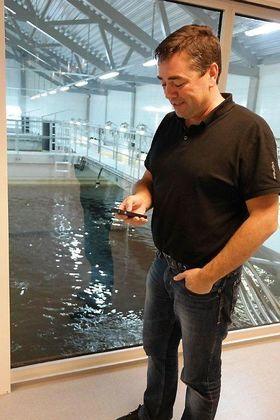 Daglig leder Erik Daaland ved Lerøy Midnor Belsvika viser hvordan han justerer foring til fisken via mobiltelefonen. Det er en stor lettelse å kunne kjøre dette på stedet i stedet for å måtte gjøre det fra kontrollrommet.